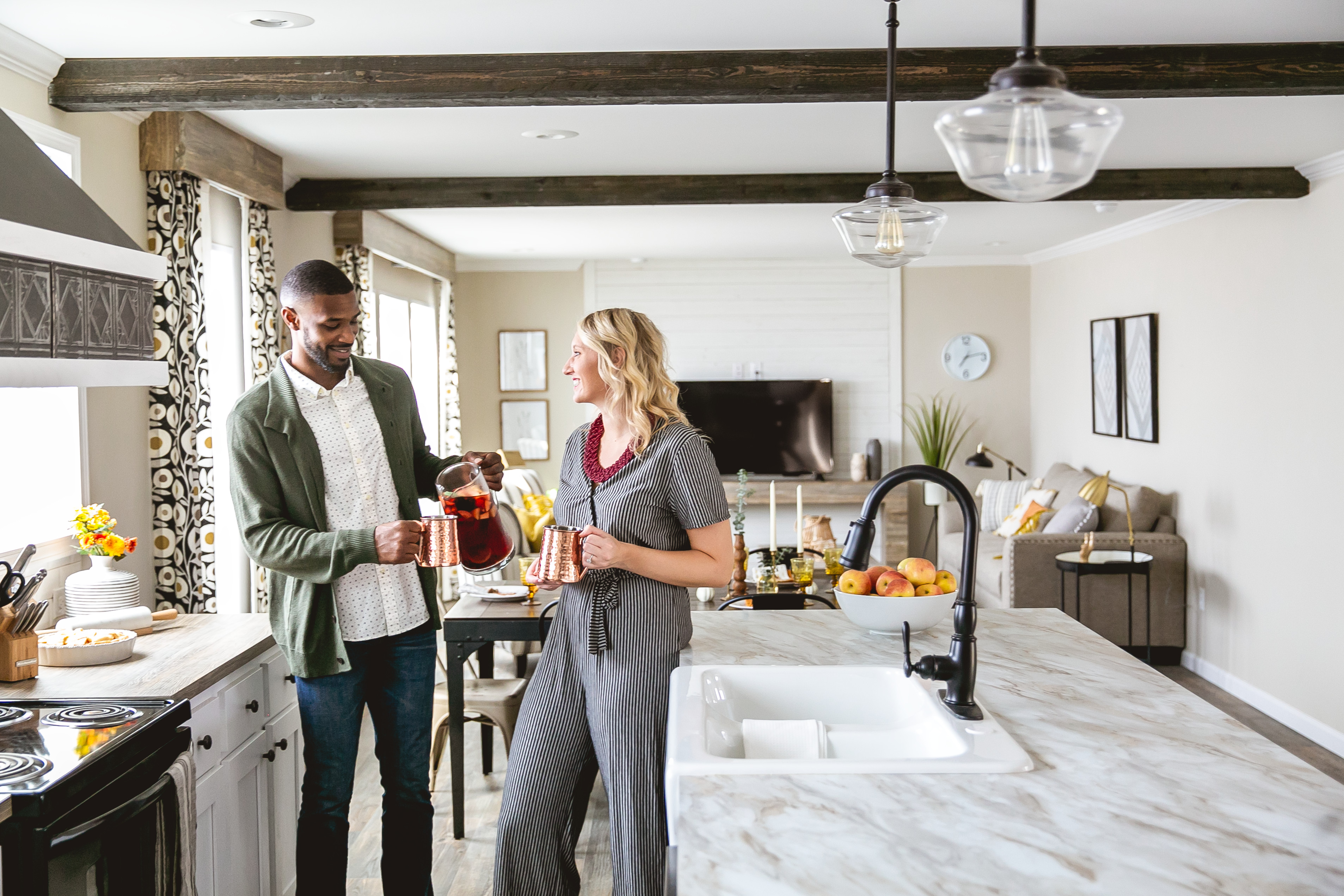 A man and woman stand in the kitchen of a new manufactured home, drinking and smiling.