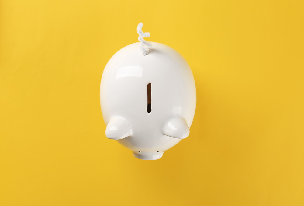 A white piggy bank against yellow background