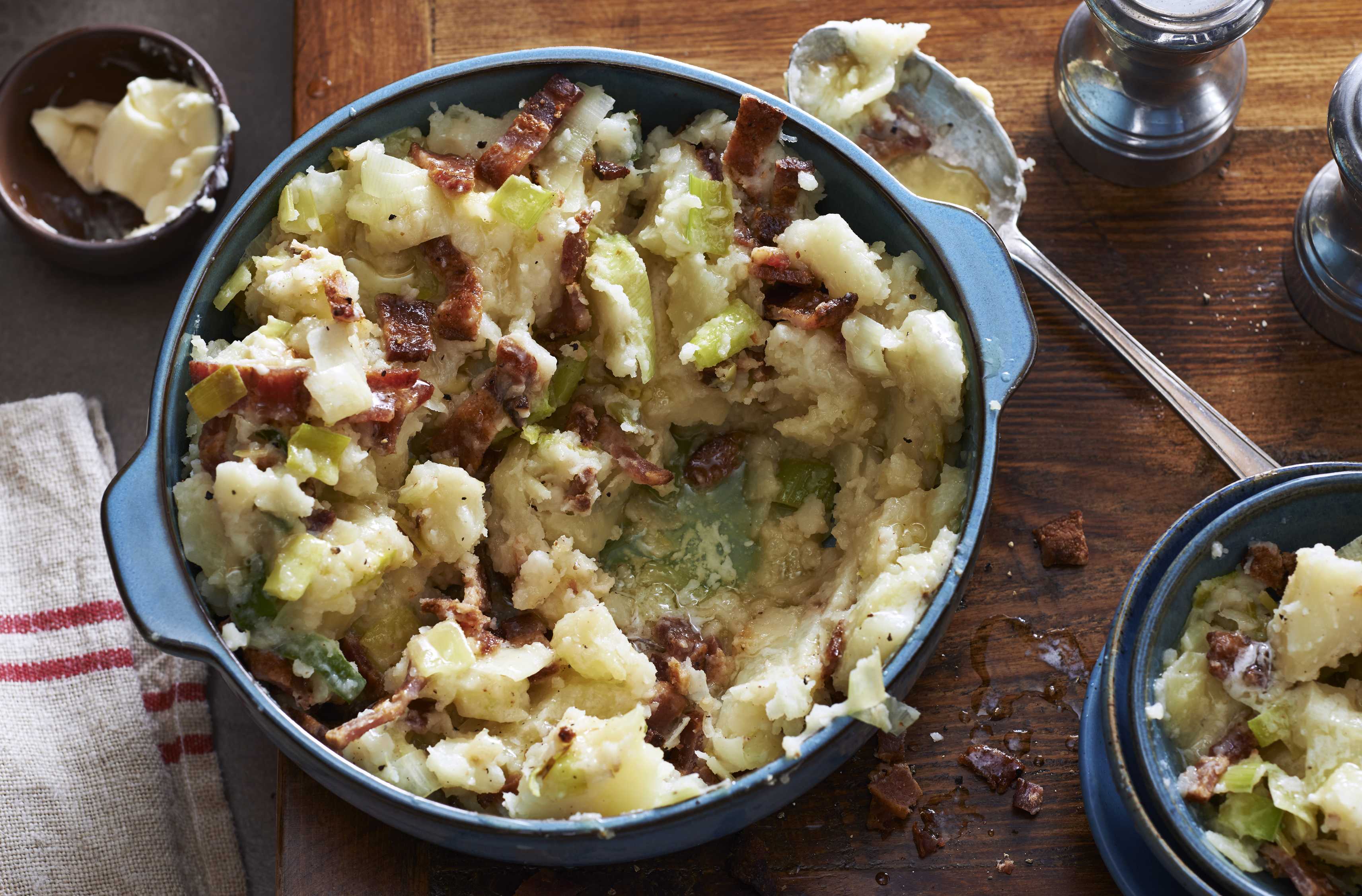 Mashed potatoes recipe mixed with leek and bacon.  Placed in a ceramic serving bowl.  Small butter dish on the side to place on top.