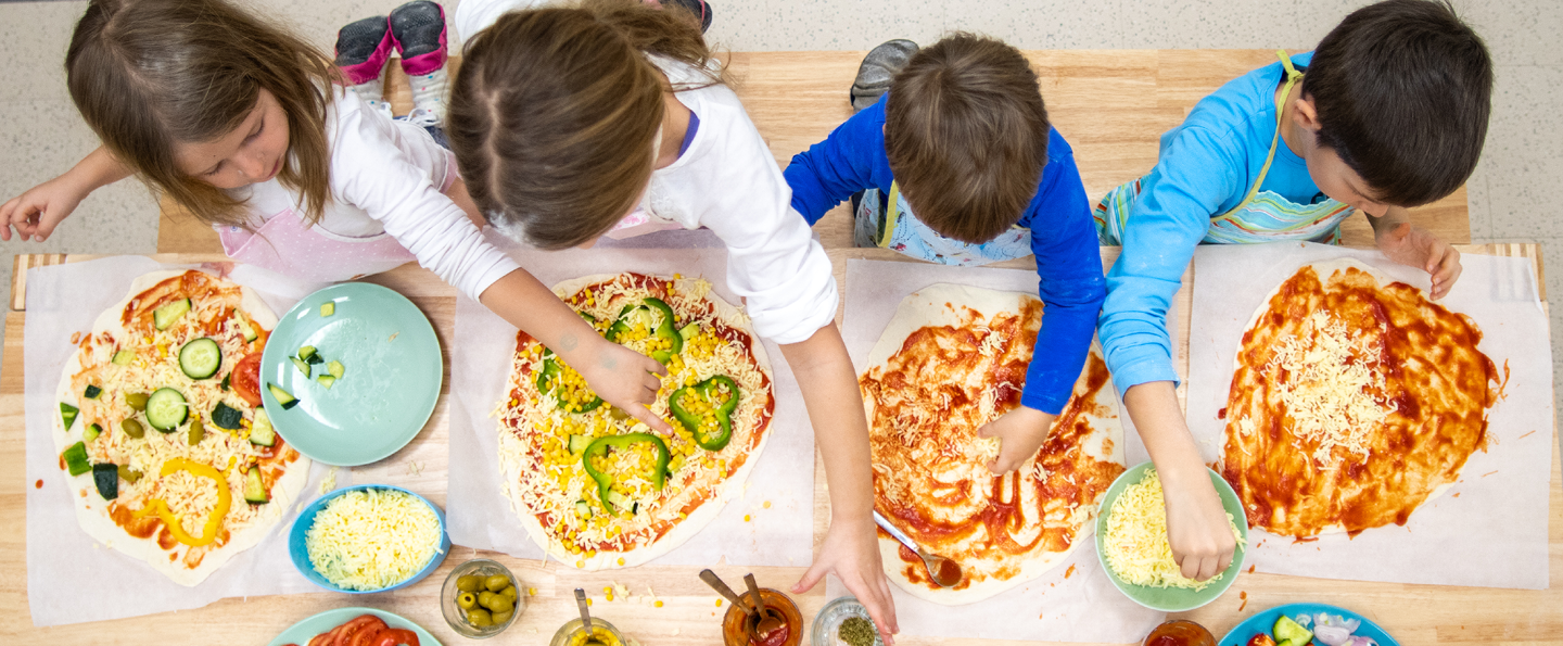 4 children making pizza at a wooden table in a cooking class with bowls of toppings and sauces and plates of sliced vegetables
