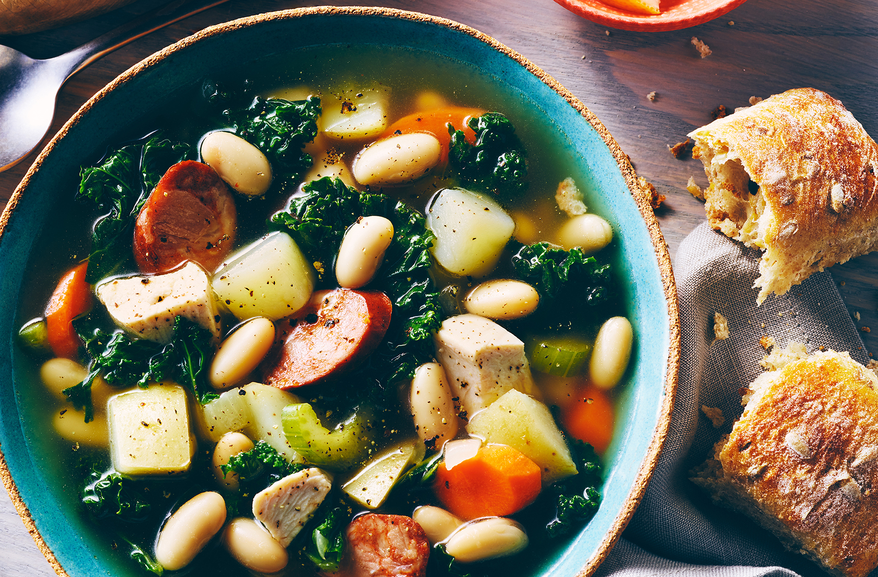 A soup of kale, chorizo, white beans, celery and potato in a clear broth