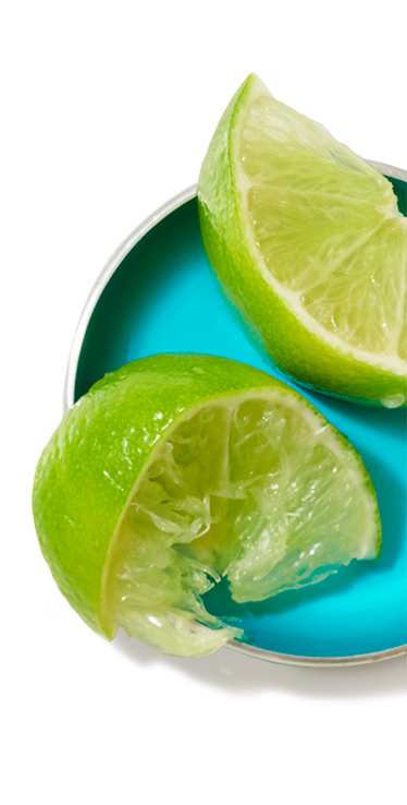 Two small lime wedges on a small dish, one which is fresh, the other previously squeezed.