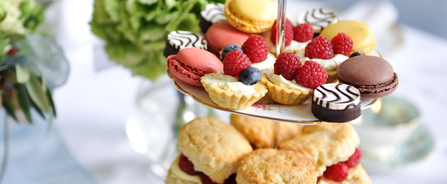 Wedding afternoon tea treats with scones, macrons and assorted pastries with floral arrangements in the background