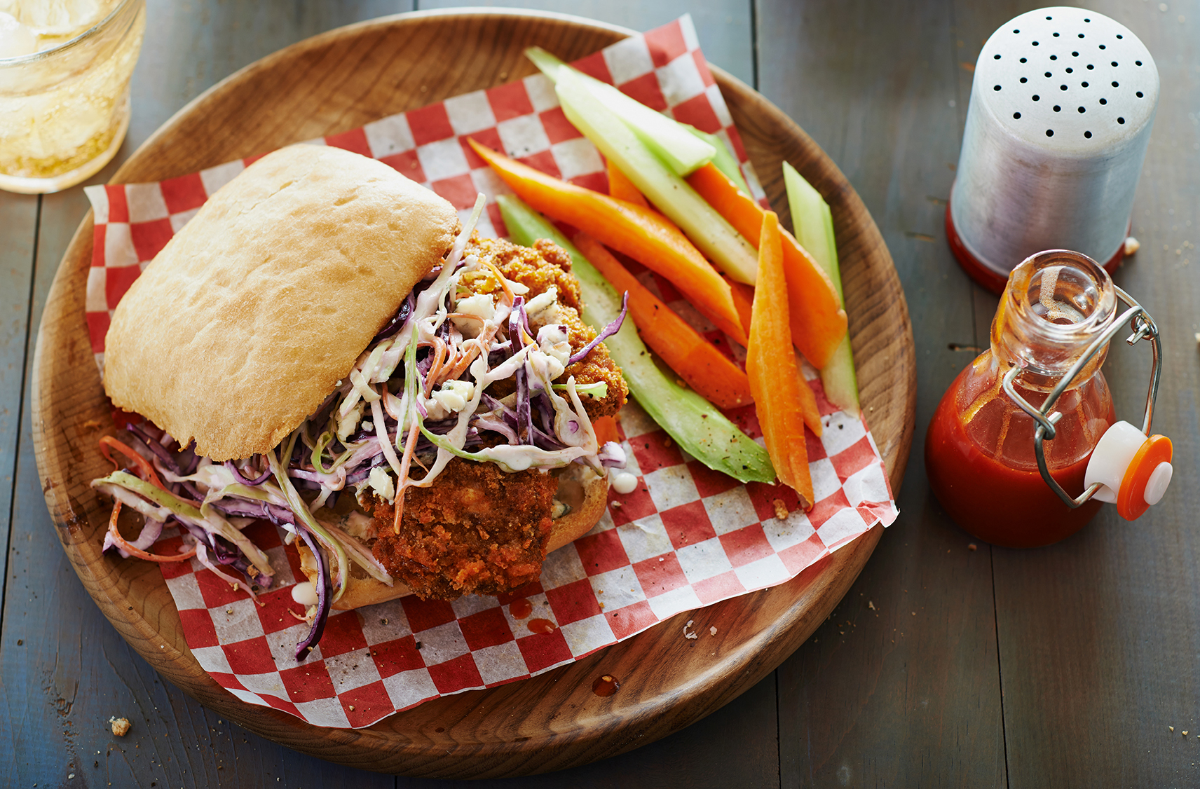 A crispy chicken sandwich on a ciabatta bun with coleslaw by carrot sticks