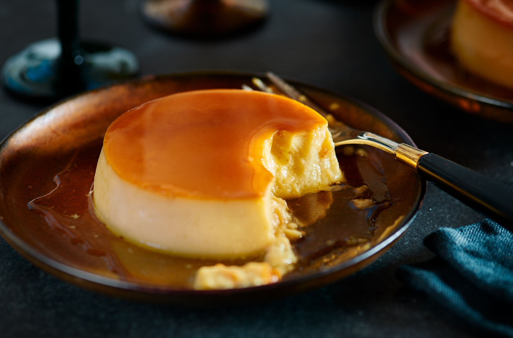 A crème caramel dessert on a plate next to a fork with 1 bite missing