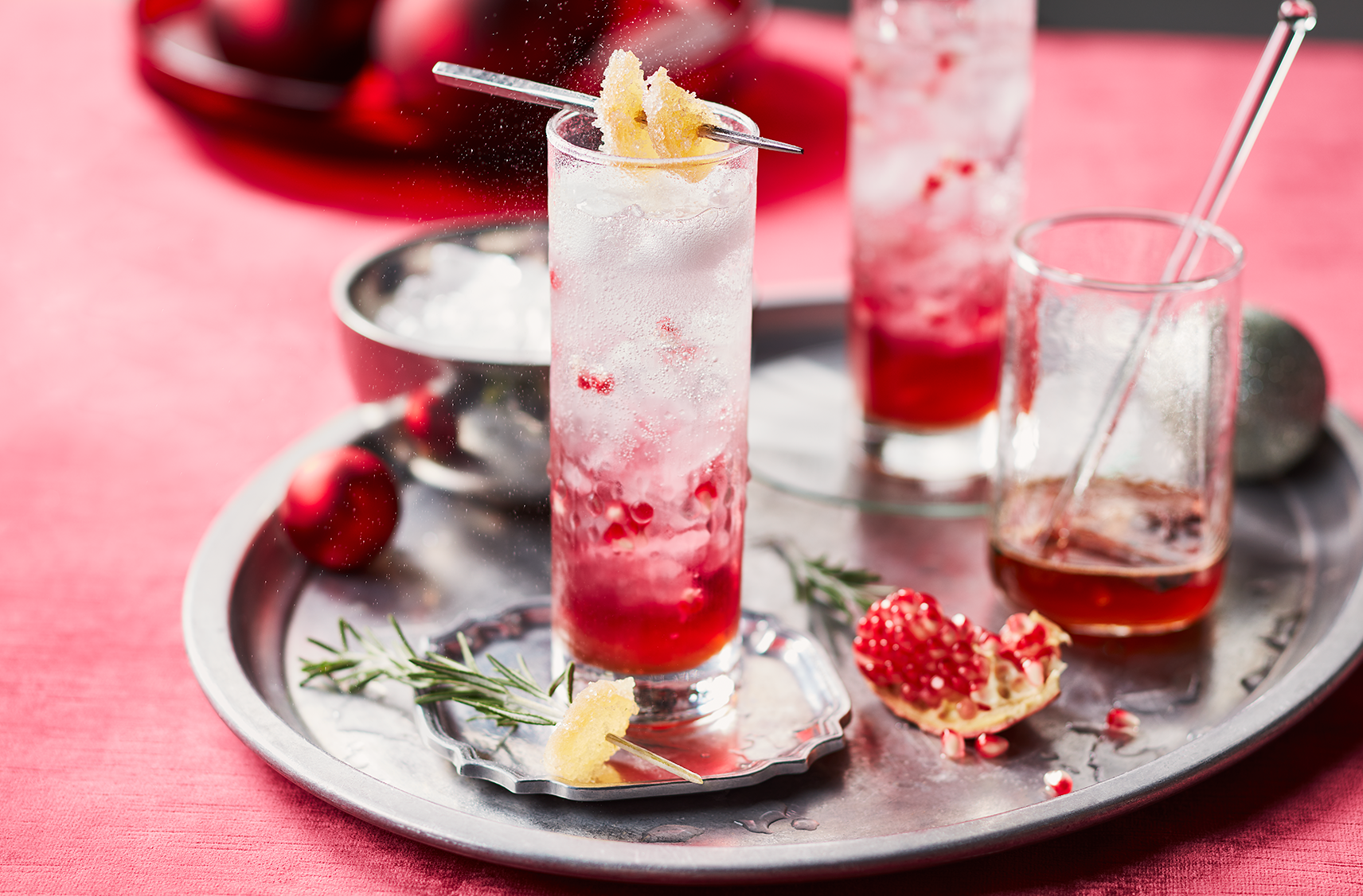 2 glasses of sparkling ginger pomegrante mocktail beverages on top of a siver serving tray with ice and syrup on the sides