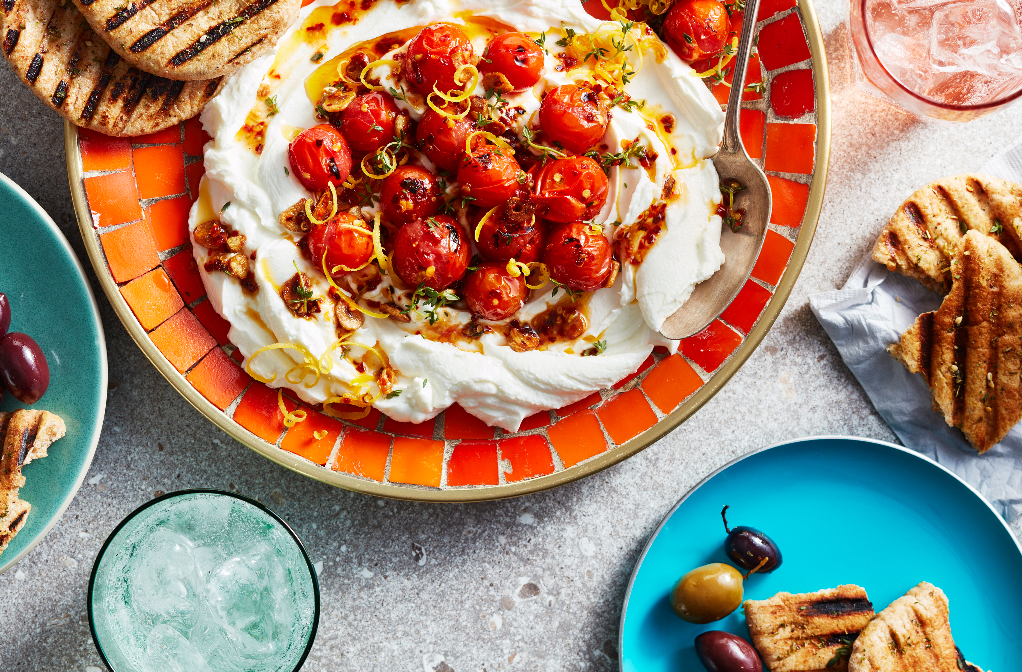 Charred axiany tomatoes nestled into a bed of plain skyr yogurt