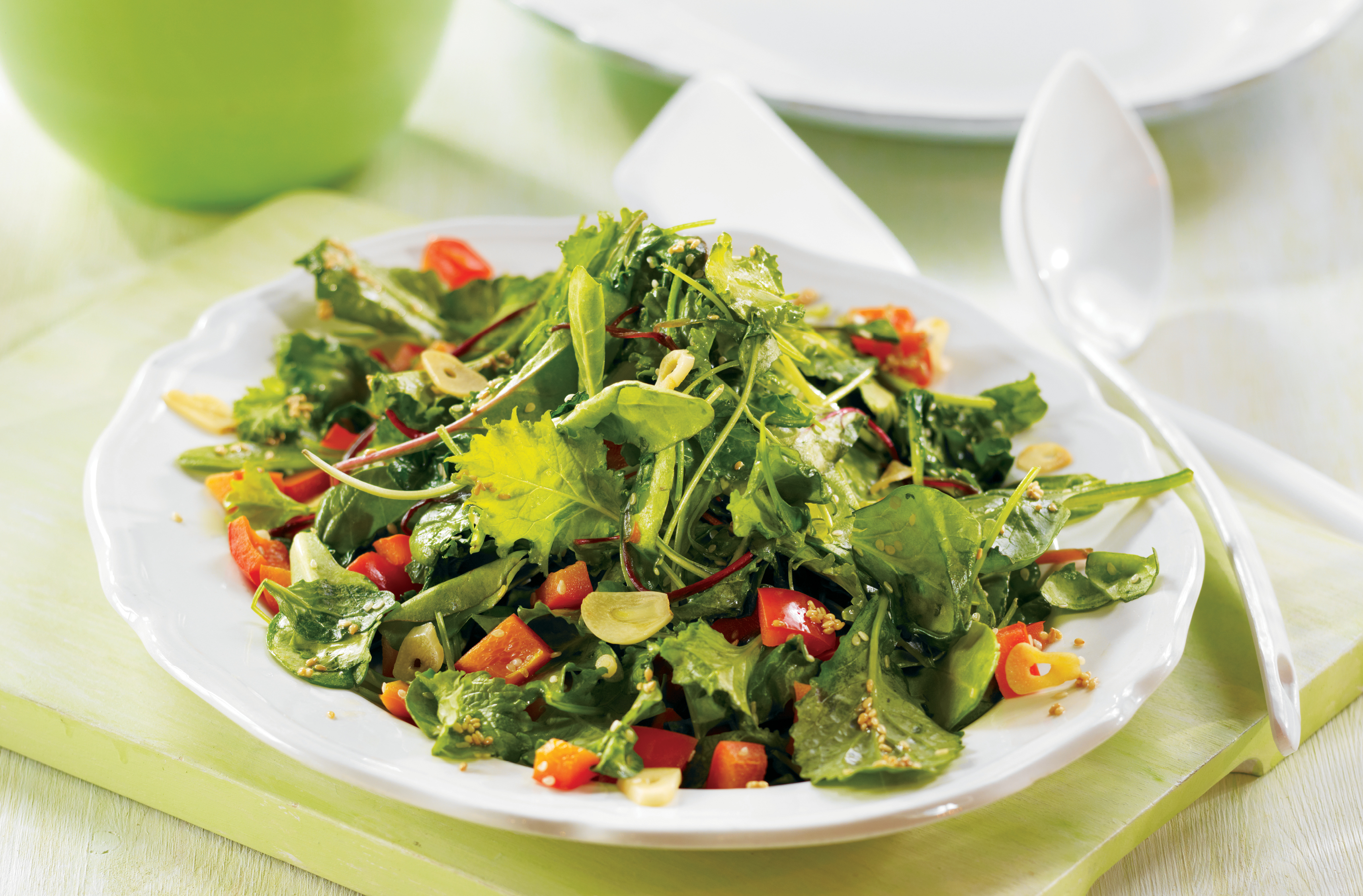 Bowl of sautéed mixed greens salad with red peppers, garlic & sesame seeds