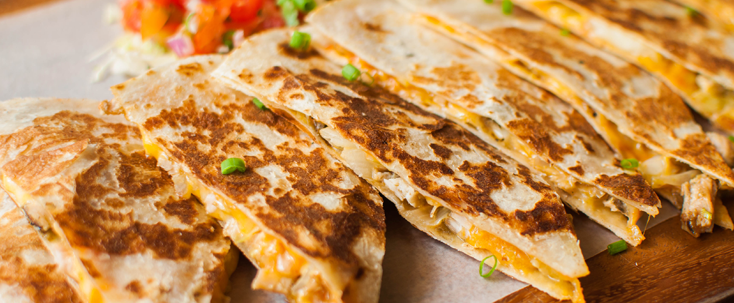 A close-up view of cheese quesadilla on a wooden dining plate