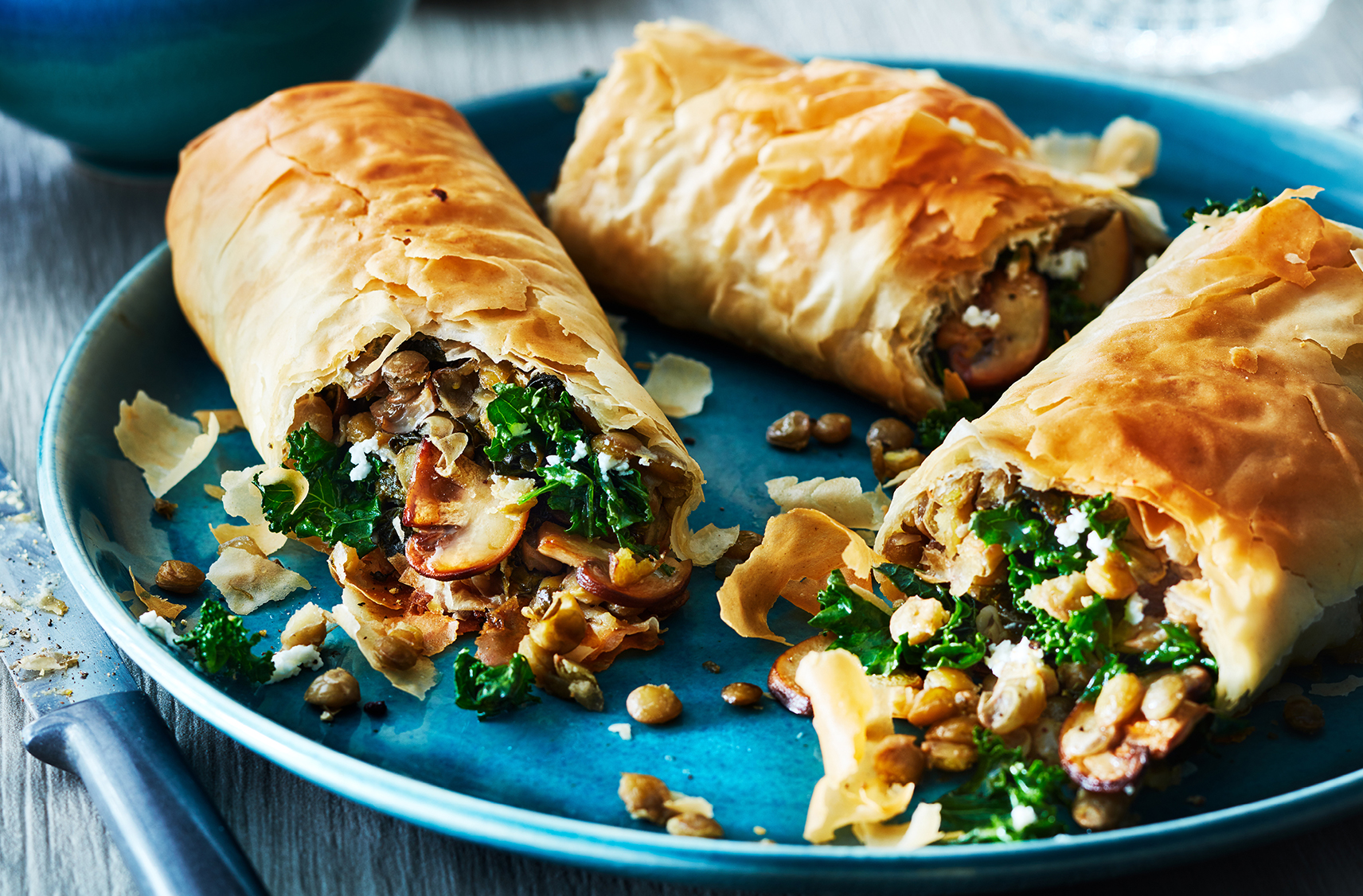three strudels stuffed with savoury kale and mushroom mixture.  served on a blue plate