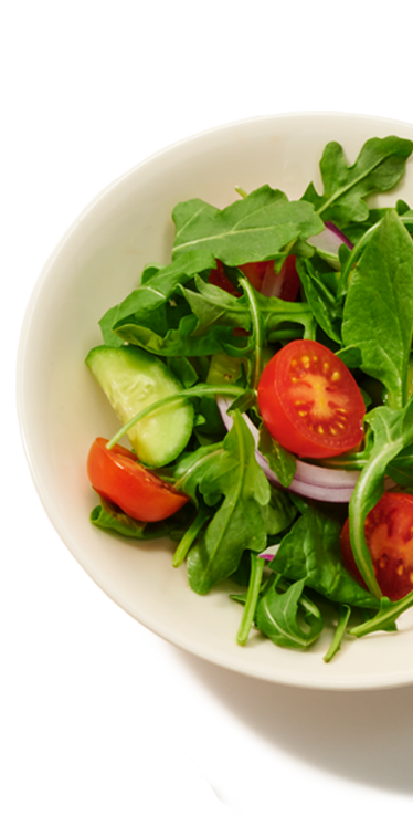 A small individual dish containing a serving of salad containing greens, tomatoes, cucumbers and red onion