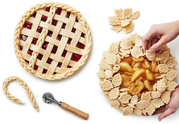 Hands preparing an apple pie with a prepared cherry pie next to it ready for baking.