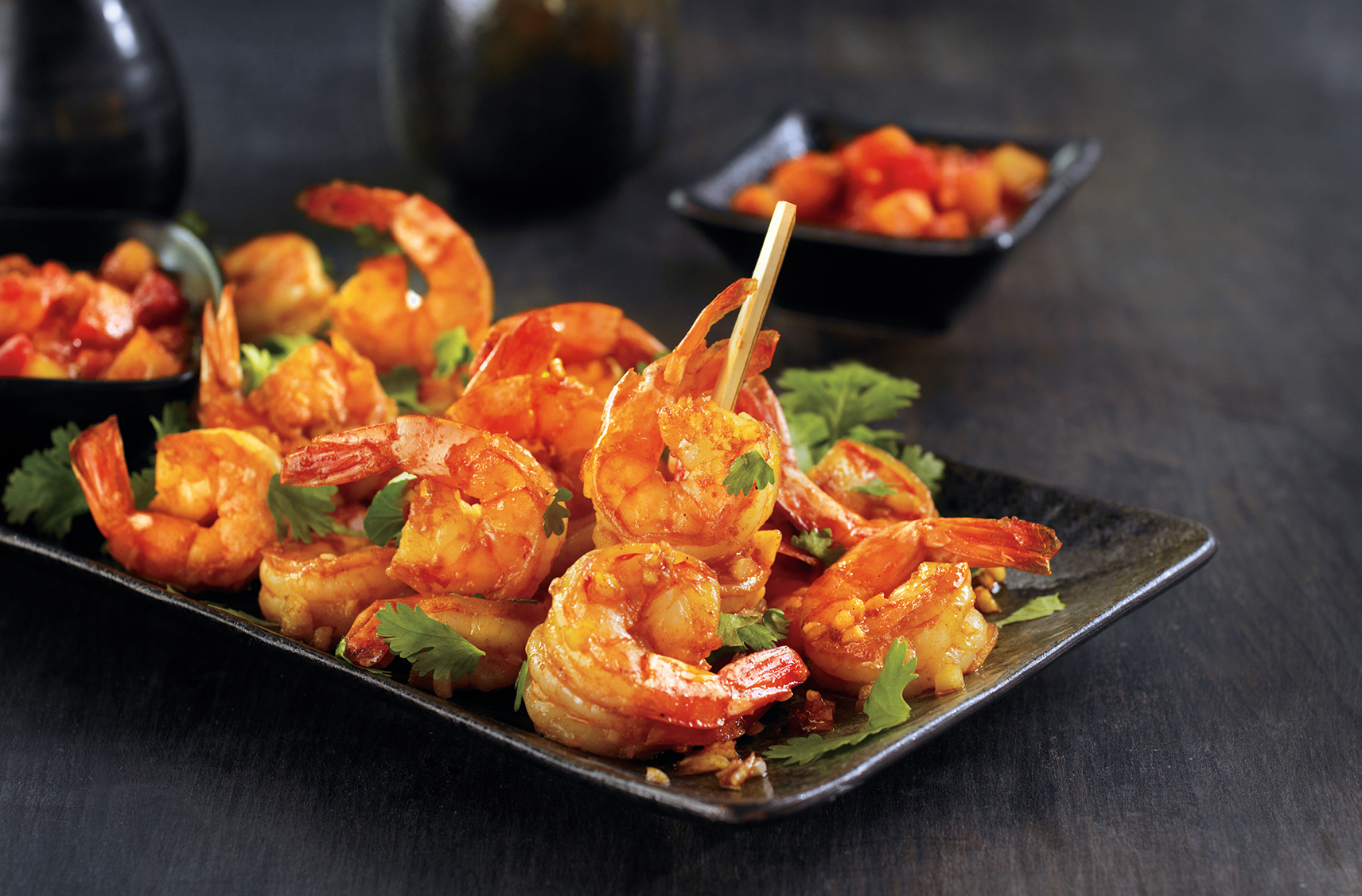 A platter of sautéed paprika-dusted shrimp by a bowl of peach mango salsa