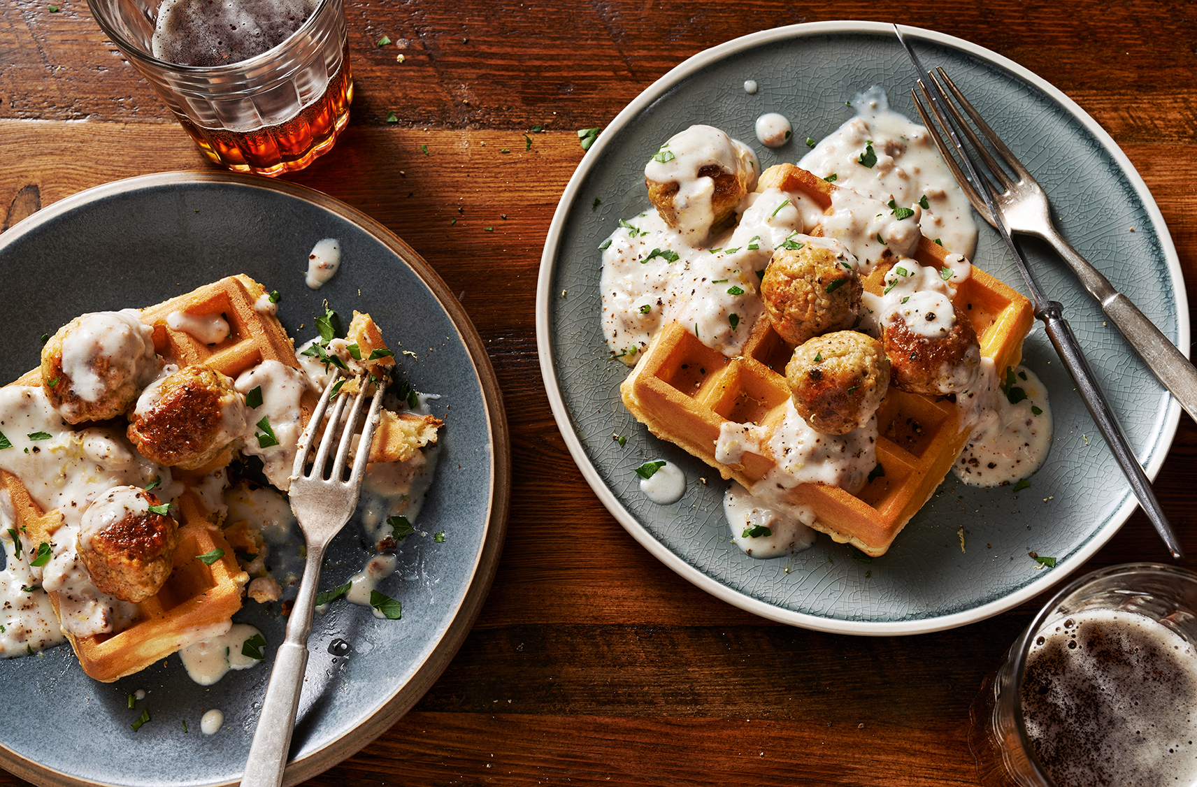 Two plates of waffles topped with chicken meatballs and gravy