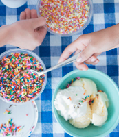 Children scooping rainbow sprinkles on bowls of ice cream.