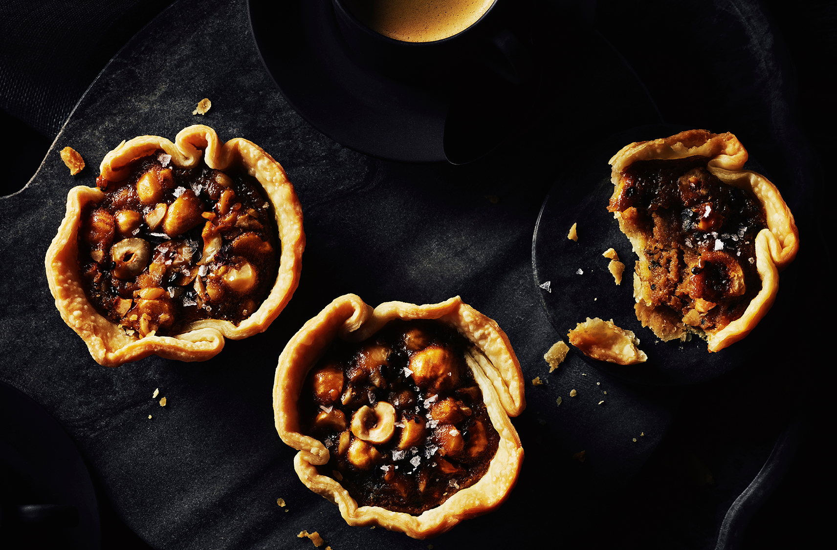 three sesame caramel hazelnut butter tarts and one has a bite taken out of it