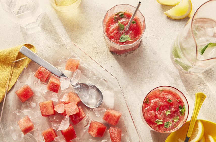 A bowl of PC Frozen Watermelon Chunks with some chunks being added to a glass of Frozen Watermelon Mint Lemonade  beside the bowl