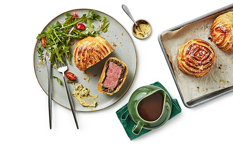 Tray of baked beef wellington on the right and a plate with field greens and a serving of beef wellington cut in half. Between the 2 there is a gravy bowl on a small towel.