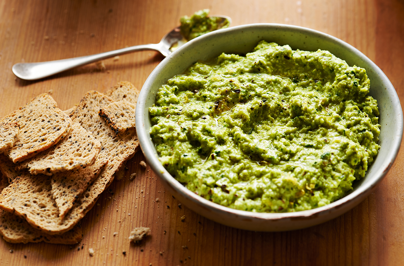 green hummus served in a small grey bowl with slices of dry toast on the side for dipping