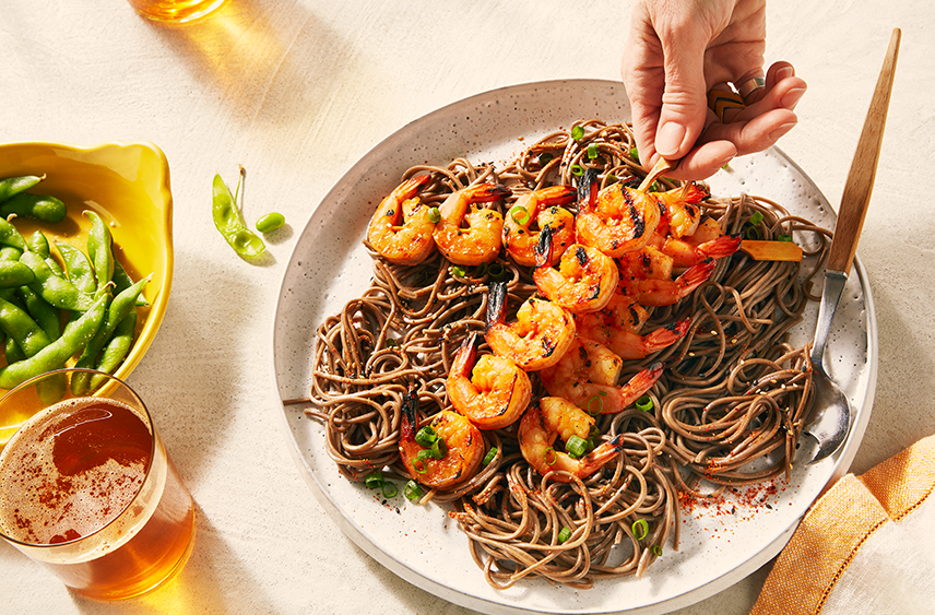 A dish of Spicy soba noodles with 3 grilled orange miso shrimp skewers being placed on top.