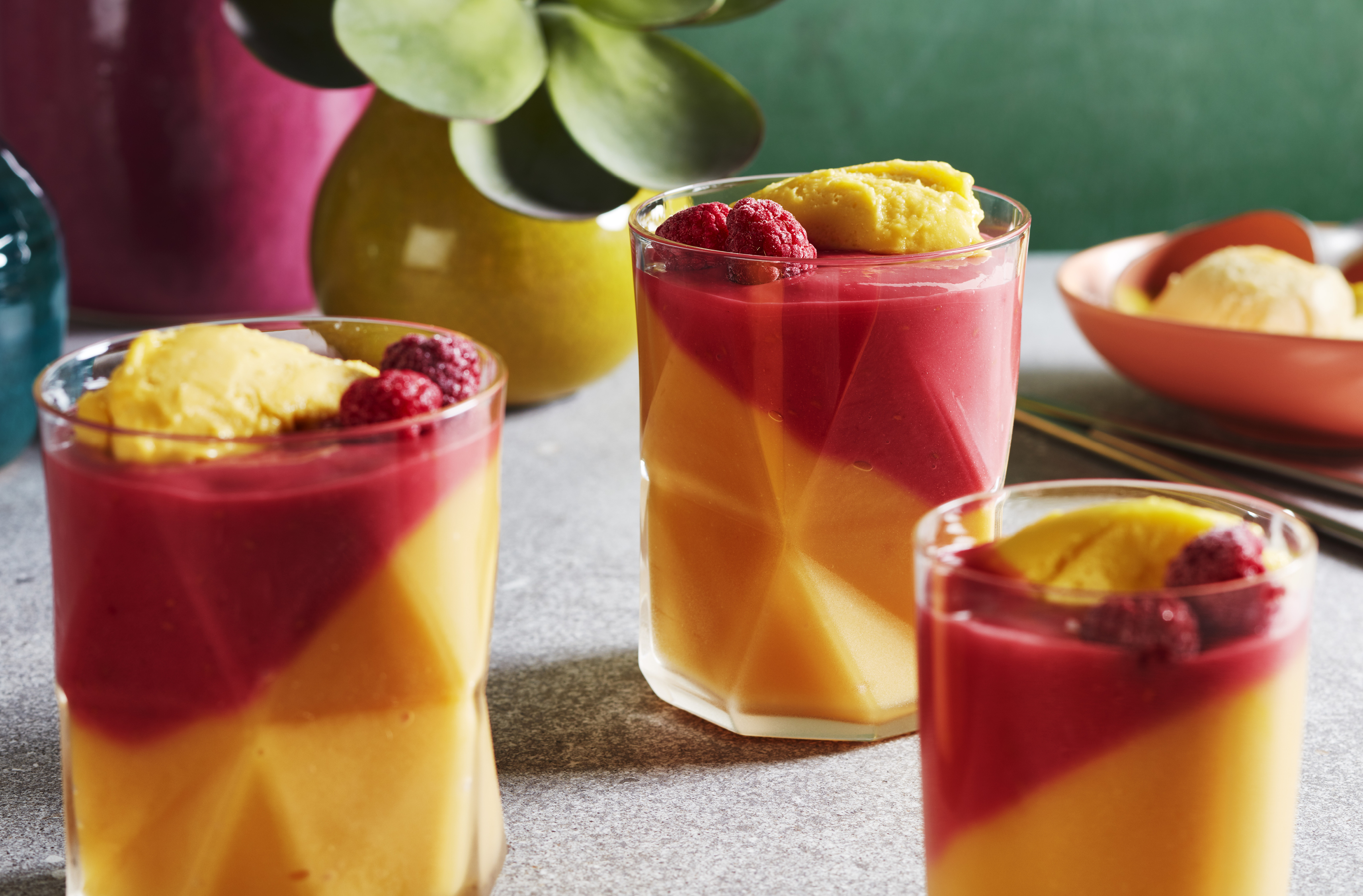 3 glasses of mango melba shake garnished with fresh raspberries