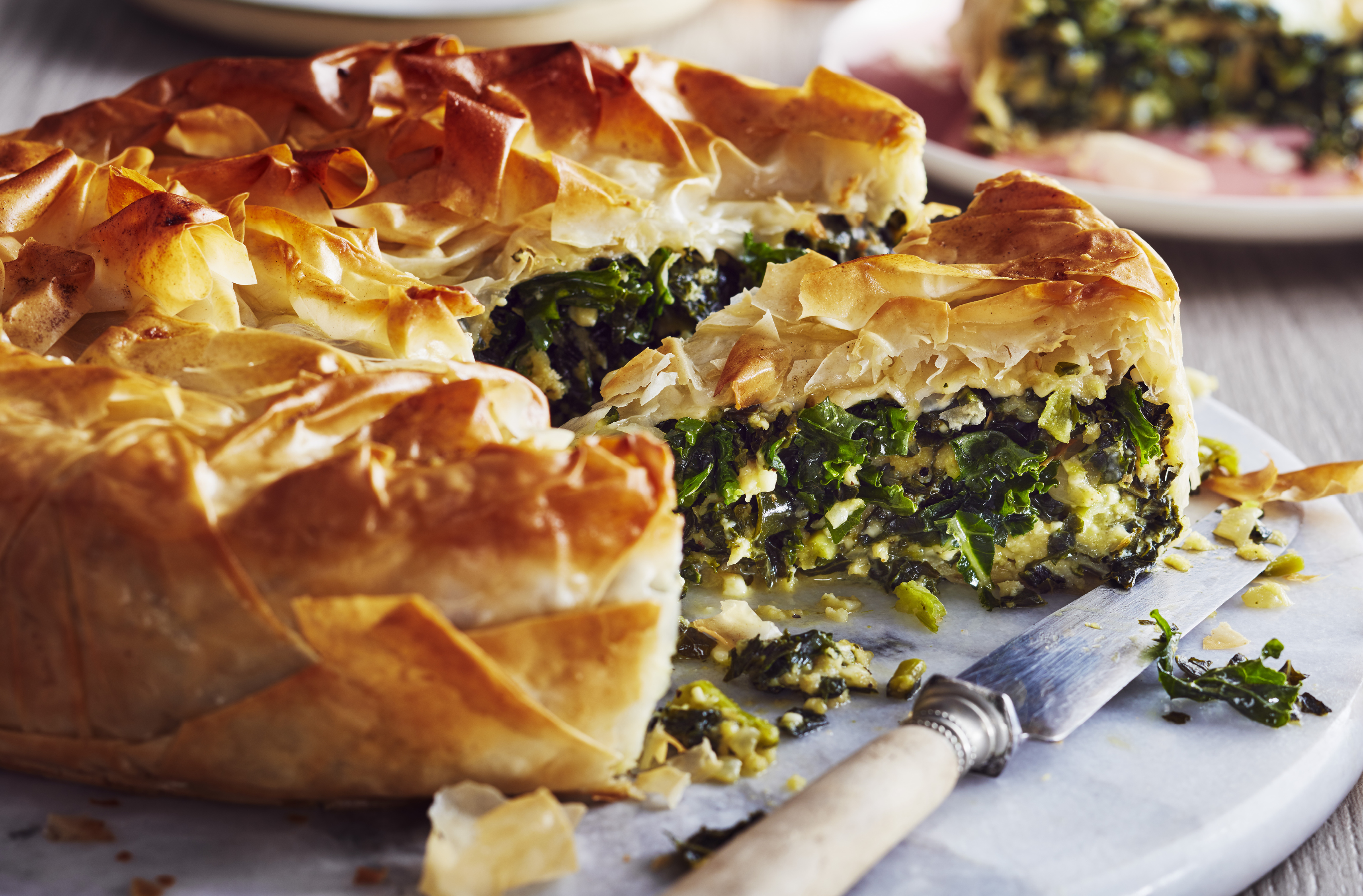 Flaky pastry encloses kale and feta in a pie shape, with one slice cut out