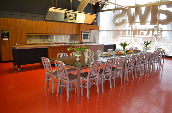 Image of an empty cooking school kitchen with a decorated table and chairs