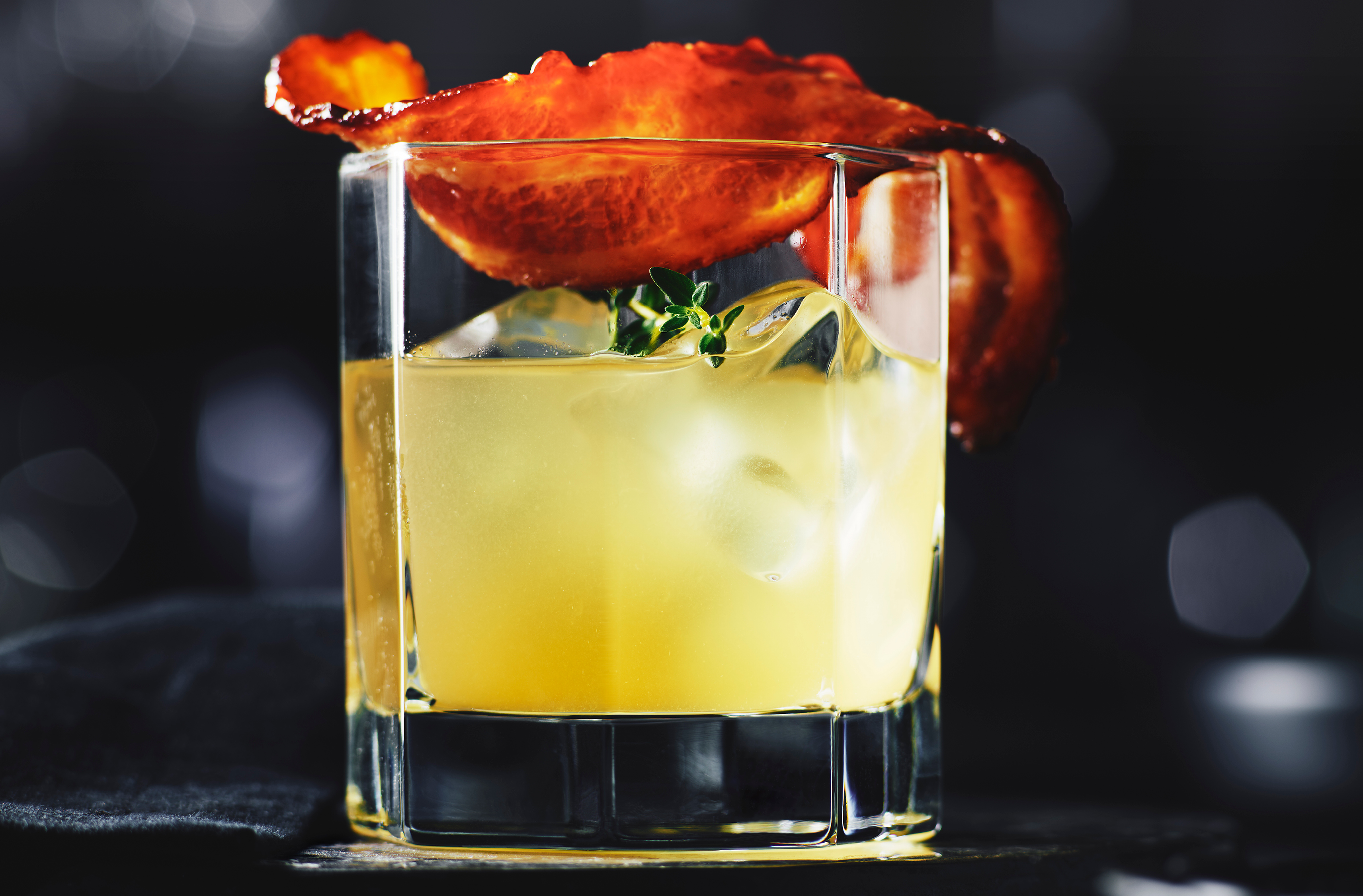 A glass of white peach bourbon shrub garnished with candied bacon