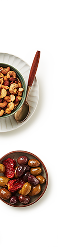 Small bowl of mixed nuts beside a smaller bowl of mixed olives.