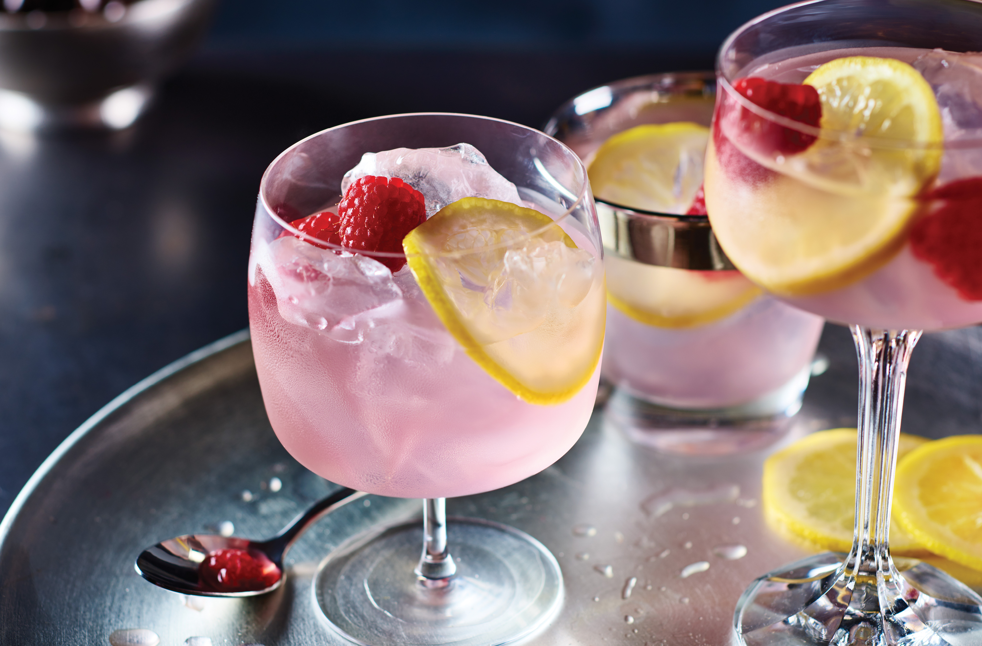 3 glasses of pink ginger kicker cocktail with raspberries and lemon slices as garnish