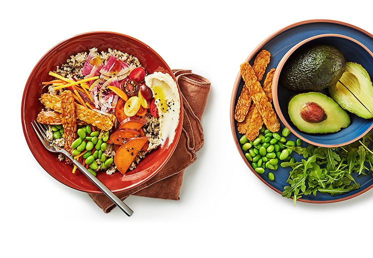 On the left a plate with quinoa, tempeh, edamame, hummus and veggies. On the right a tray with tempeh, edamame, greens with a bowl of halved avocados.