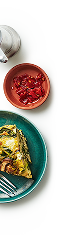 A plate with a serving of egg and mushroom frittata, beside a small dish of red pepper.