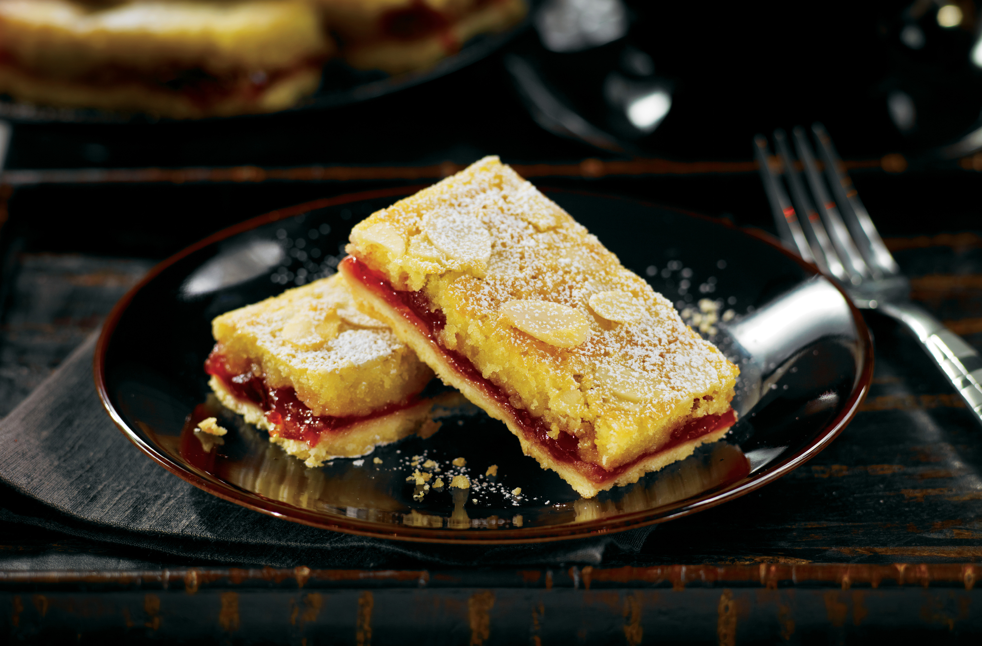 2 dessert squares with cherry centre topped with almond slices
