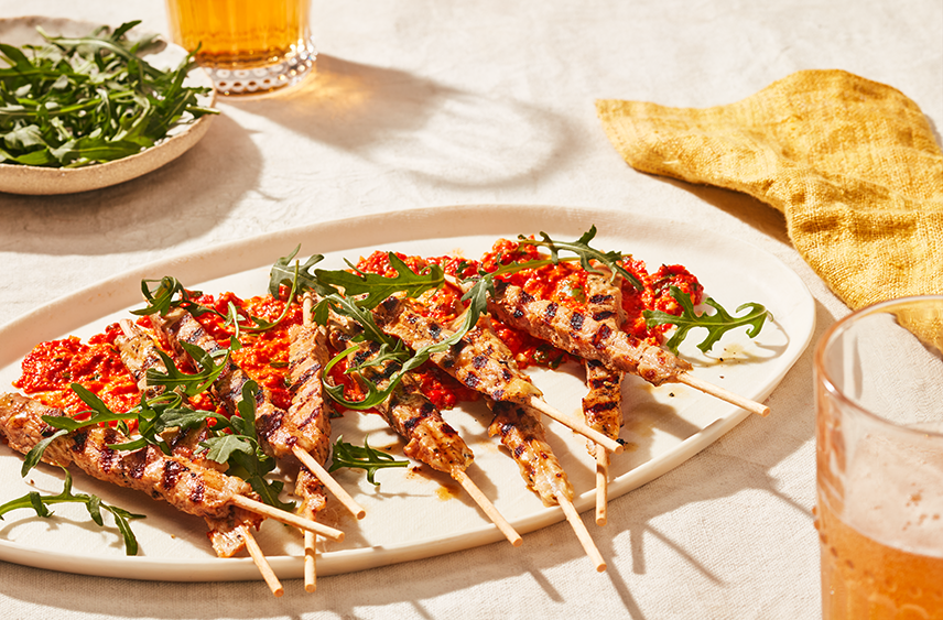 A plated filled with skewers of cubed grilled chicken wrapped in bacon topped a romesco sauce and sprigs of arugula.