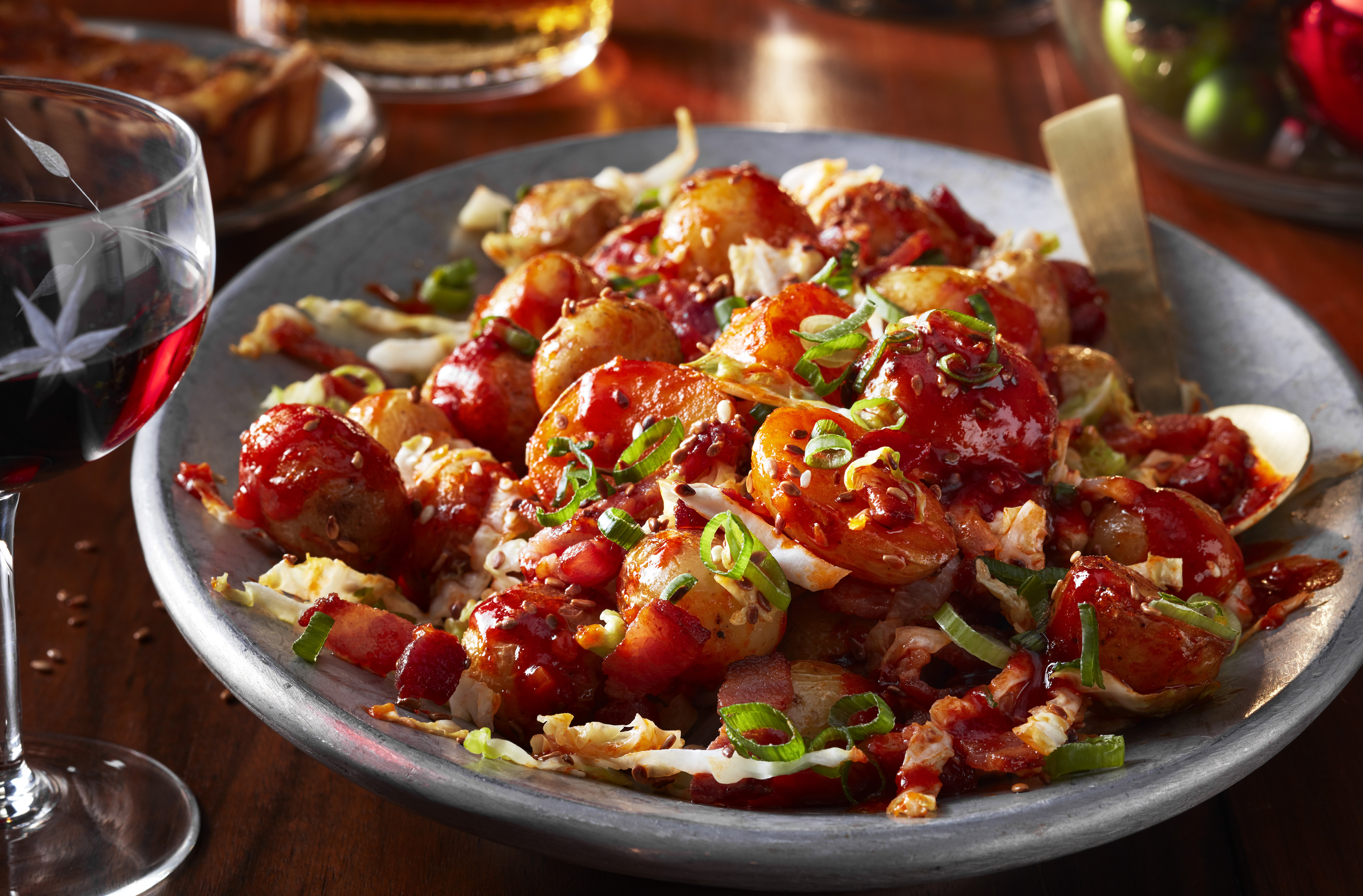 A platter of korean fried potatoes topped with bacon and scallions