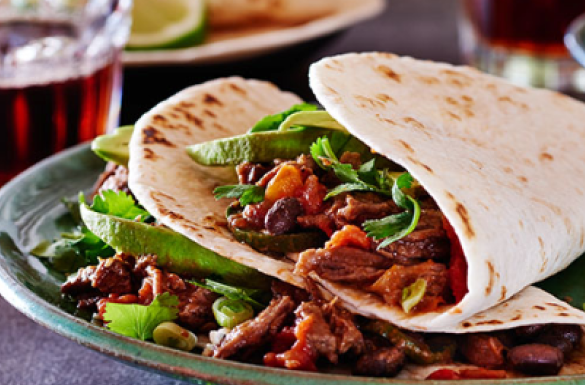 Two soft tortillas filled with seasoned strips of stewing beef and veggies.