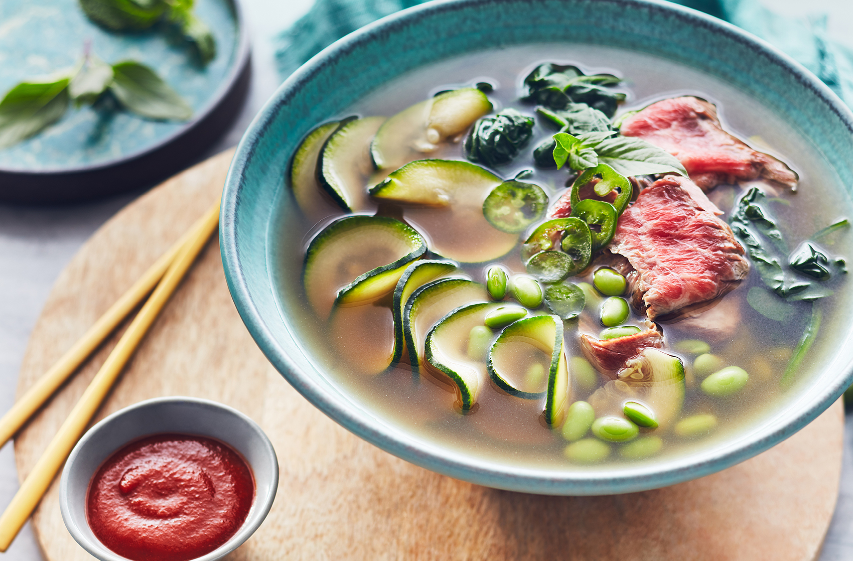 Chopsticks rest by a bowl of broth with zucchini noodles, red beef and veg