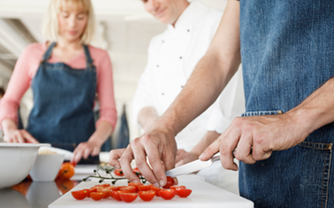 Chef and couple in kitchen slicing tomatoes