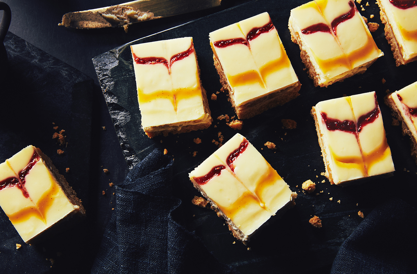 raspberry blonde chocolate cheesecake squares placed on black slate tray for presentation