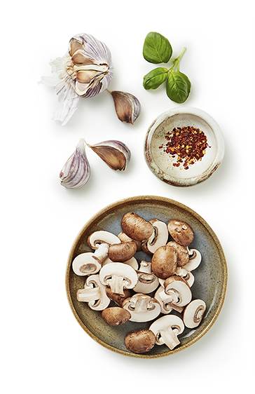 a small plate of sliced mushrooms surrounded by a small bowl of chili pepper seeds, garlic clove with pieces separated.
