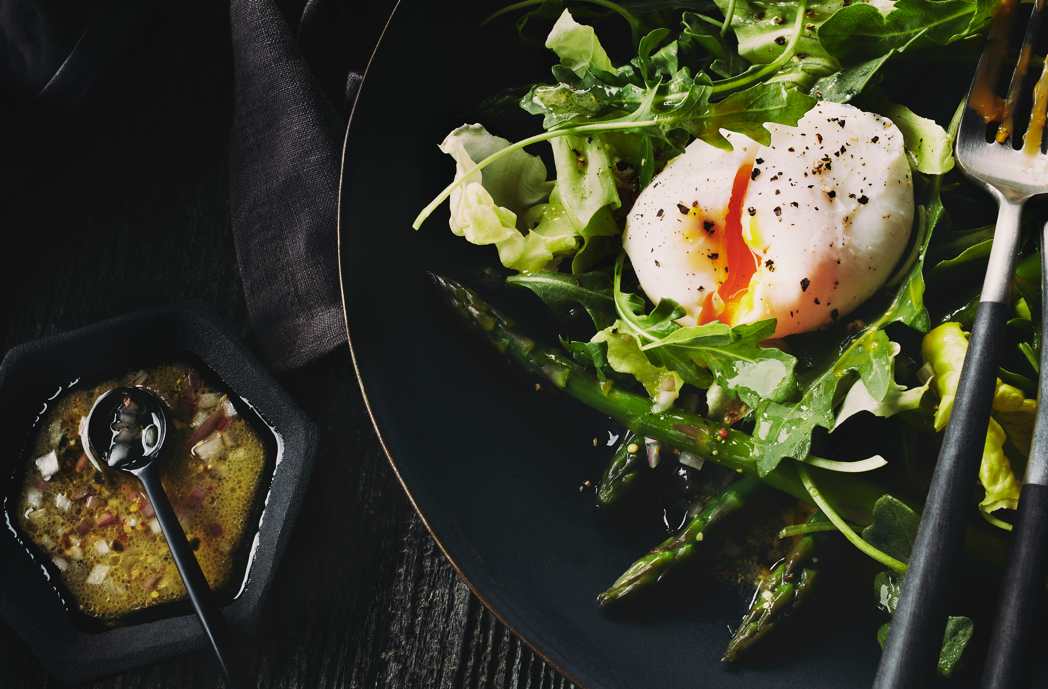 A plate of asparagus and mixed greens topped with umami aioli & a poached egg