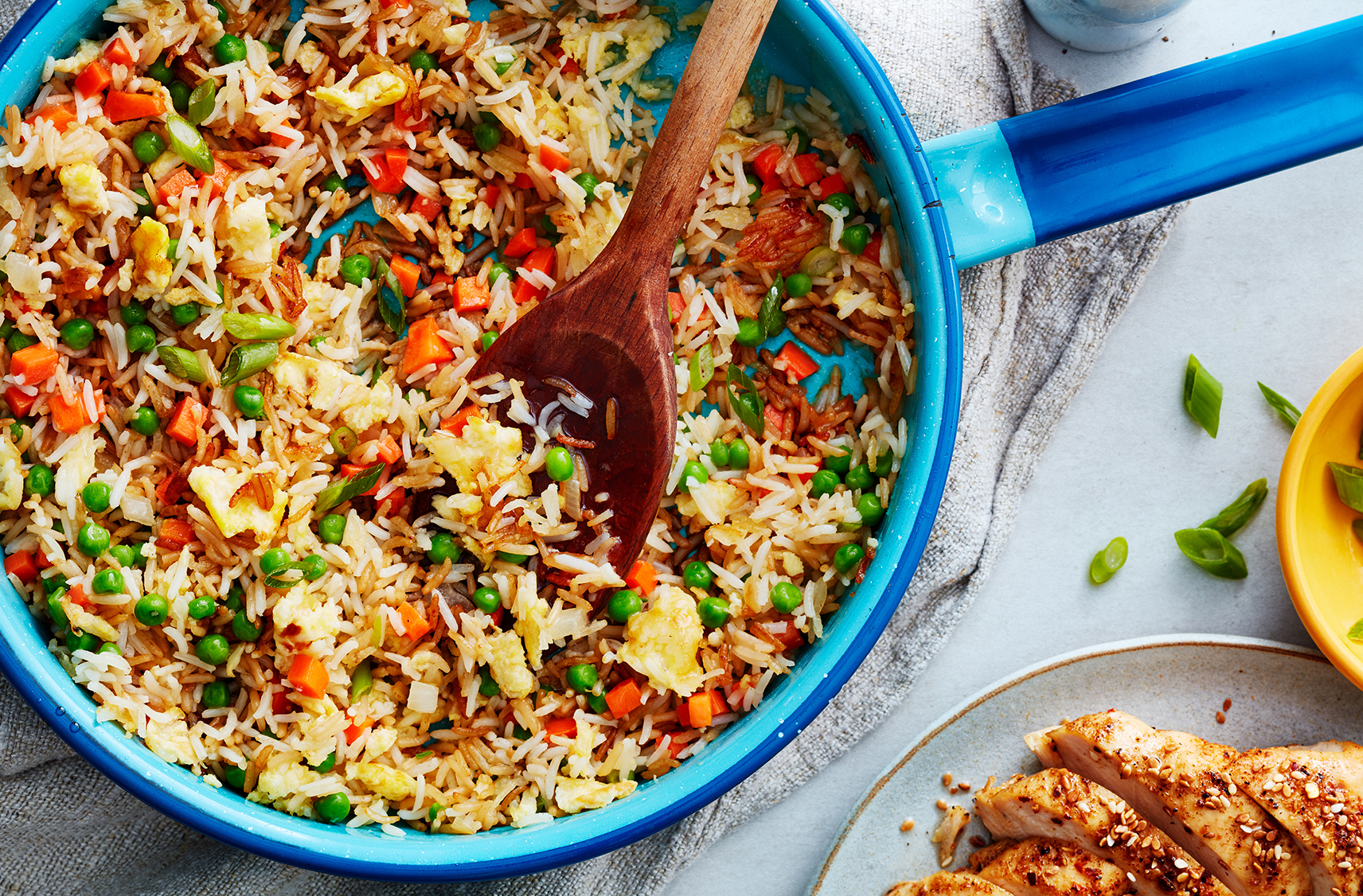 A spoon scoops up fried rice with diced carrot and peas from a blue skillet