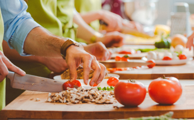 Group of people wearing aprons taking part in cooking class, preparing food, slicing vegetables. Close up of hands. Unrecognizable people.