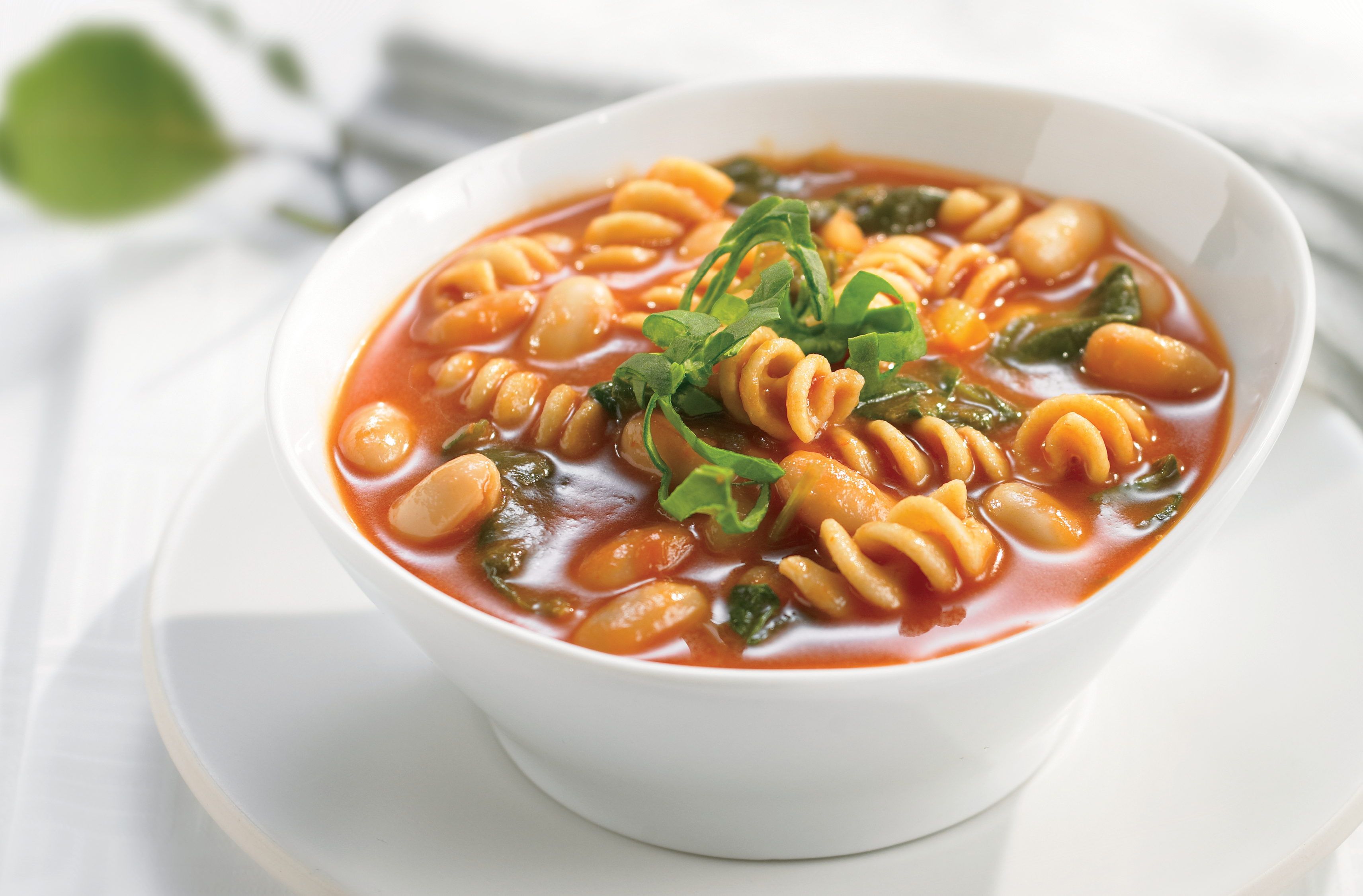 A bowl of rotini & kidney bean vegetable soup with onion, celery & spinach