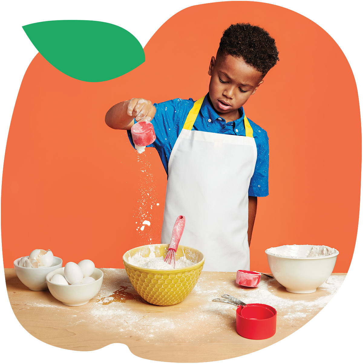 A young boy baking, misting flour and eggs on a counter in mixing bowls and measuring cups in the background of an animated image of an apple