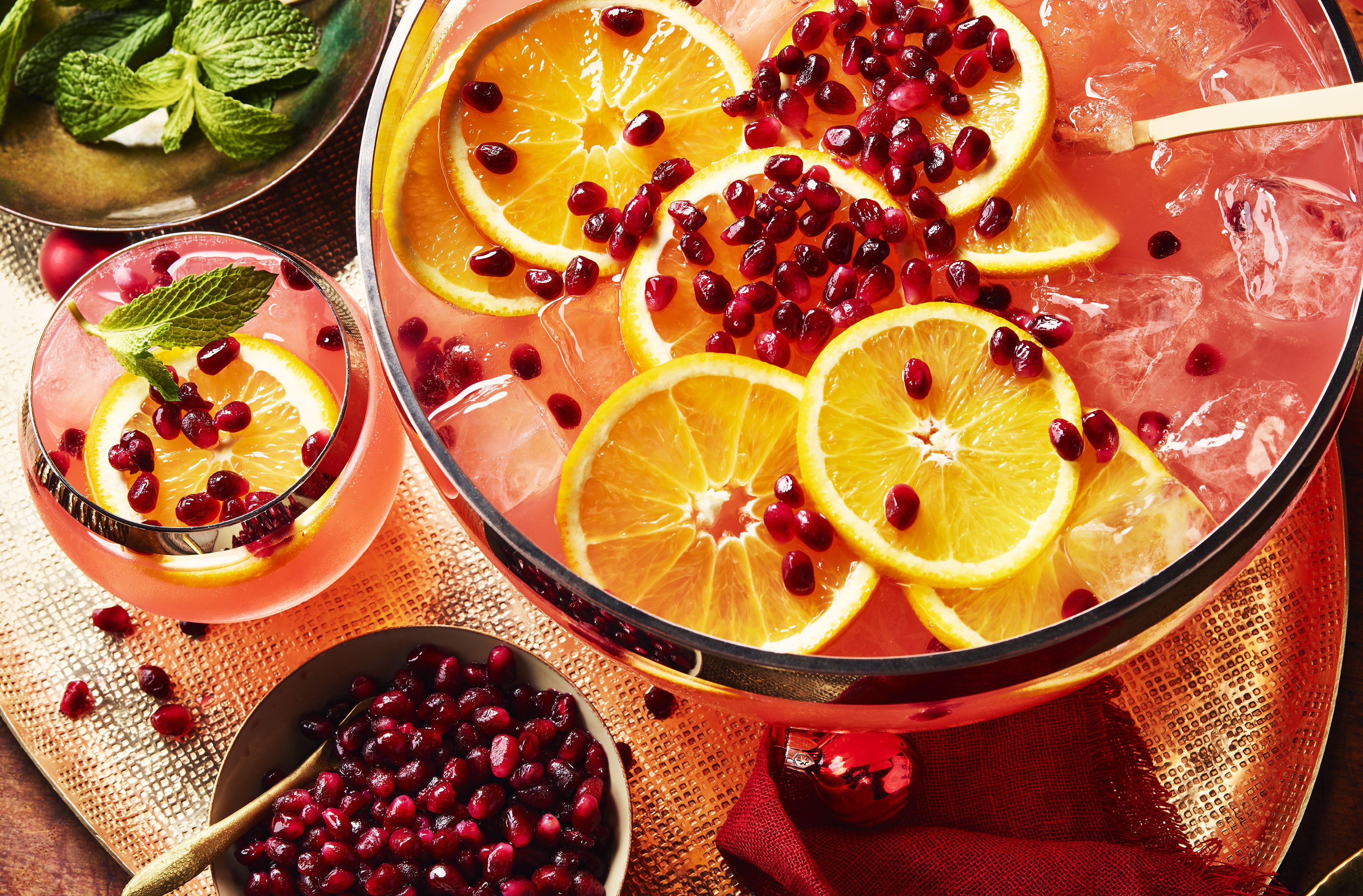 Pomegranate seeds, orange and ice float in a punch bowl beside mint leaves