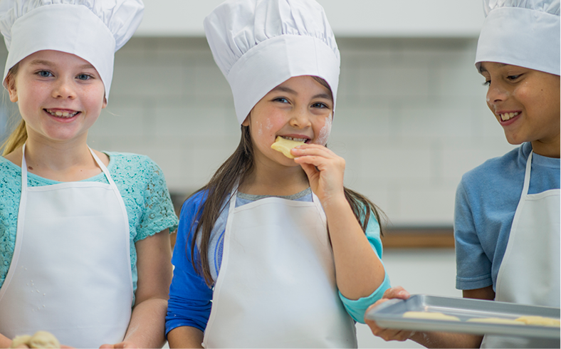 A group of elementary age children are learning how to cook in the kitchen. They are wearing aprons and chefs hats and are testing food.