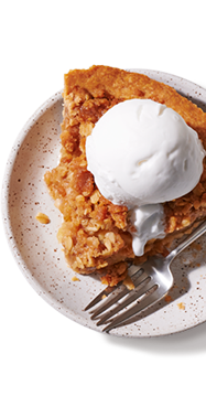 A slice of plant-based apple pie a la mode on a plate ready to be served
