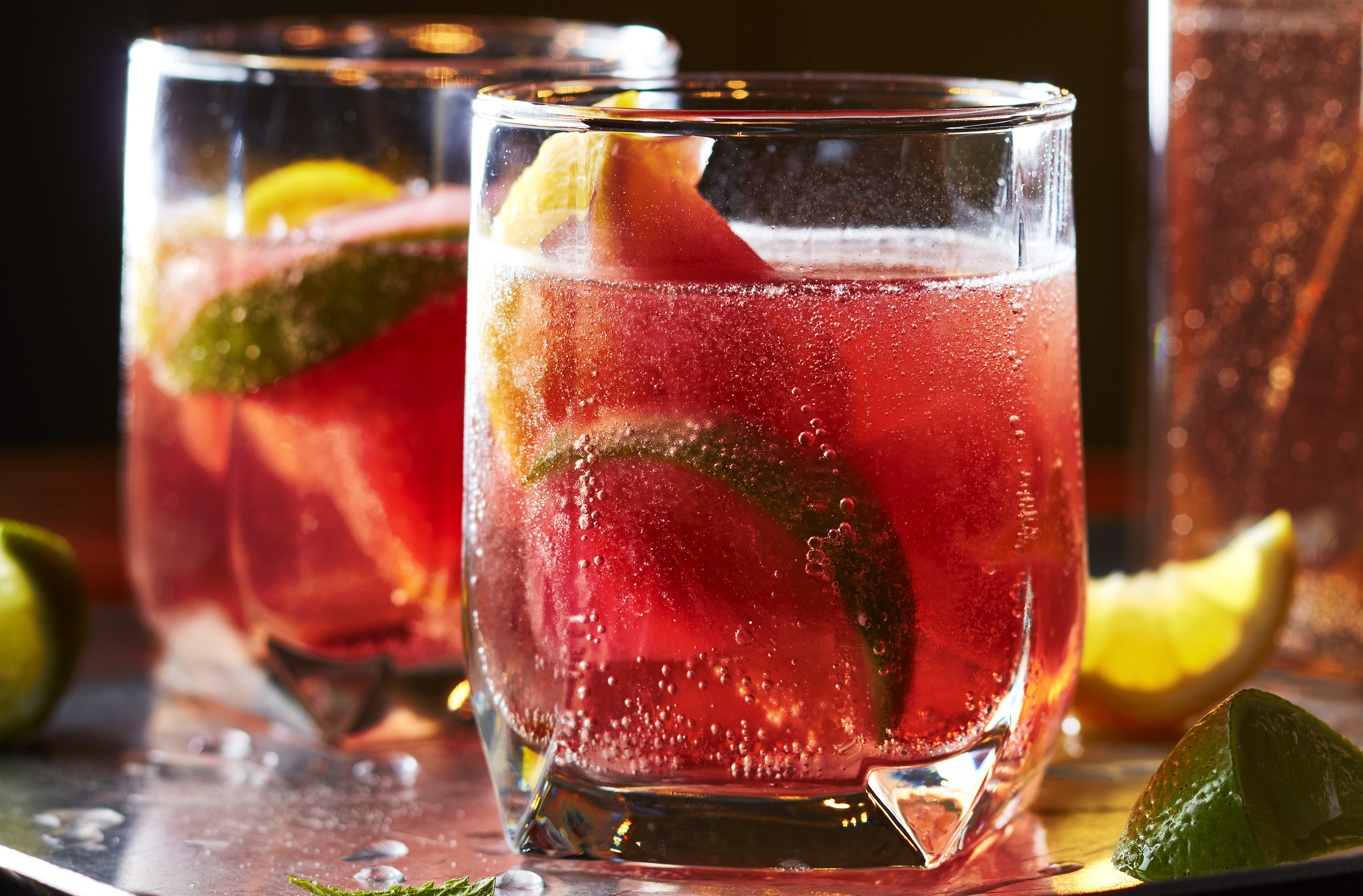 Two glasses of Ginger Hibiscus Sparkling Punch with slices of lime inside