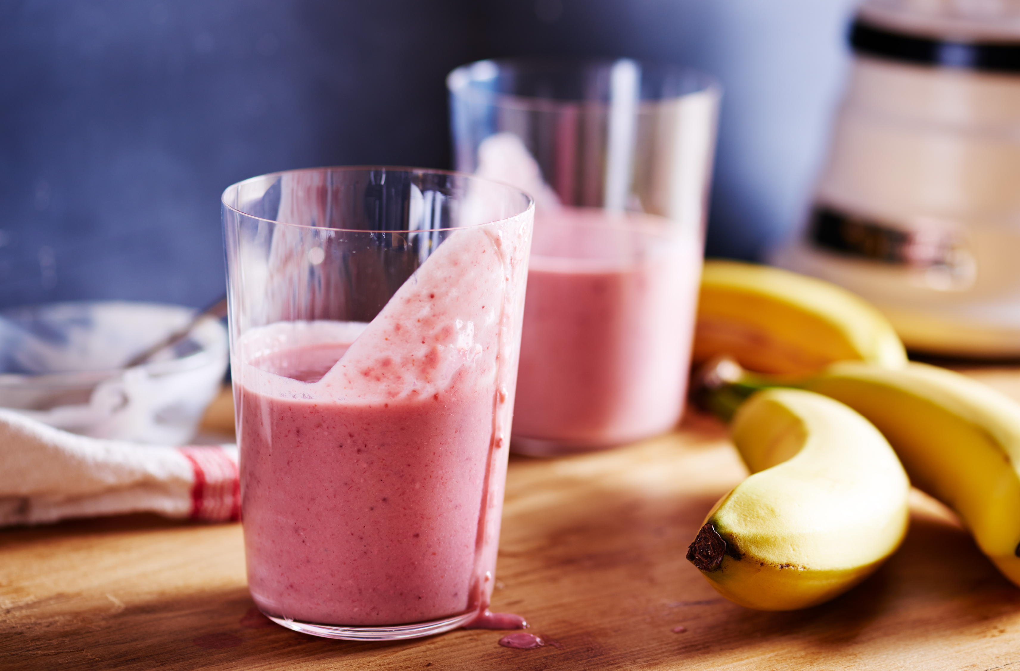 2 glasses of strawberry cashew breakfast shake on a table beside 2 bananas